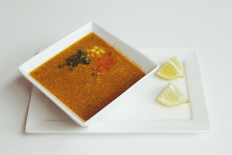 Spicy corn and bell pepper soup with lemon wedges
